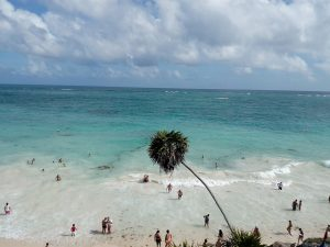 Turistas se refrescan de las altas temperaturas en la playa del sitio arqueológico de Tulum, en la suroriental península de Yucatán, una zona de México muy vulnerable al cambio climático. Huracanes poderosos, tormentas, sequía, olas de calor y subida del nivel del mar constituyente efectos del cambio climático que impactan la salud mental de la población del país. Crédito: Emilio Godoy/IPS