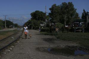 Una mujer camina cerca de las vías de un tren en Palma Soriano, en el este de Cuba, donde el gobierno del municipio, como los de los otros 167 municipios del país, se prepara para asumir las nuevas prerrogativas de autonomía establecidas por la Constitución que el país estrena el 10 de abril. Crédito: Jorge Luis Baños/IPS