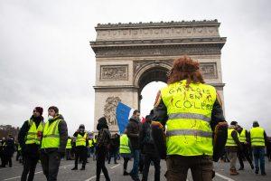 """Miembros de los """"chalecos amarillos"""" durante una de sus jornadas de protesta en París, ante el Arco de Triunfo. Crédito: Olivier Ortelpa/CC By 2.0"""