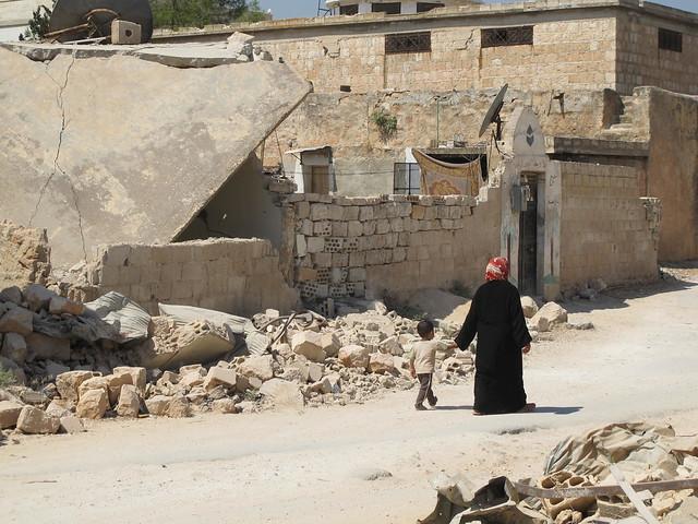 Una madre y su hijo caminan entre edificios derruidos en Ma'arat Al-Numan, en una foto de 2013. El colapso en los servicios de gestión de desechos, a menudo interrumpido debido a los combates, también puede conducir a la contaminación y los riesgos para la salud, lo que representa un desafío no solo para los civiles que permanecen en Siria sino también para aquellos que desean volver. Crédito: Shelly Kittleson/IPS