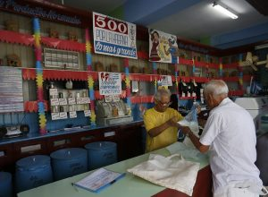 Un cliente recibe arroz en una bodega estatal, que suministra los alimentos a precios subsidiados incluidos en la libreta de racionamiento, cuya eliminación se aleja ante el recrudecimiento de la crisis económica en Cuba. Crédito: Jorge Luis Baños/IPS