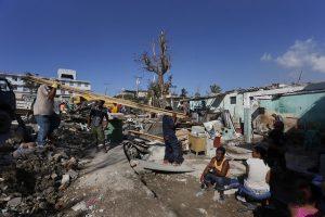 Varias personas permanecen alrededor de sus destruidos hogares el 28 de enero, en un barrio del municipio de Regla, mientras trabajadores laboran en la reconstrucción de las viviendas, dañadas por el tornado que el día antes azotó cinco de los 15 municipios de la capital de Cuba. Crédito: Jorge Luis Baños/IPS