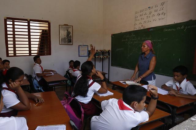 Una maestra imparte clases a estudiantes de enseñanza primaria, en una escuela en la ciudad de Baracoa, en la oriental provincia de Guantánamo. Los docentes y otros empleados del aparato público del Estado de Cuba se benefician desde este mes de julio del incremento salarial decidido por el gobierno. Crédito: Jorge Luis Baños/IPS