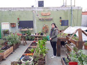 Milagros Sánchez, coordinadora del biosistema urbano que funciona en un comedor comunitario de Ciudad Oculta, en el sur de la capital de Argentina, enseña la huerta en cajones que funciona sobre su techo. En ella se cultivan verduras y hortalizas y también hongos comestibles a partir de residuos. Crédito: Daniel Gutman/IPS