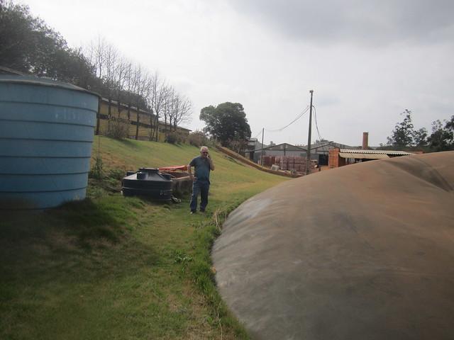 Romário Schaefer, de 65 años, entre el biodigestor negro enterrado en la tierra, el depósito azul del suero lácteo que se mezcla con excrementos de los cerdos que ceba en una hilera de pocilgas (arriba a la izquierda) para producir biogás, en el municipio de Entre Rios do Oeste, en el sur de Brasil. Al fondo su fábrica de ladrillos, que consume el combustible y con el que ahorra unos 6.500 dólares mensuales de electricidad. Crédito: Mario Osava/IPS