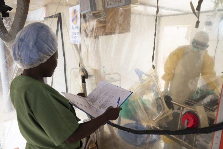 Trabajadores de salud hablan con un paciente de ébola que permanece aislado, en un Centro de Tratamiento de Ébola, en Beni, República Democrática del Congo. Se han encontrado dos medicamentos para tratar con éxito al letal virus, porque permite a las comunidades el tratamiento temprano de los enfermos. Crédito: OMS