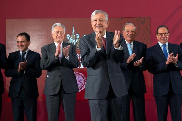 El presidente Andrés Manuel López Obrador, en el centro, aplaude con el magnate Carlos Slim, detrás a su derecha, durante la rueda de prensa del 27 de agosto. Crédito: Presidencia de México