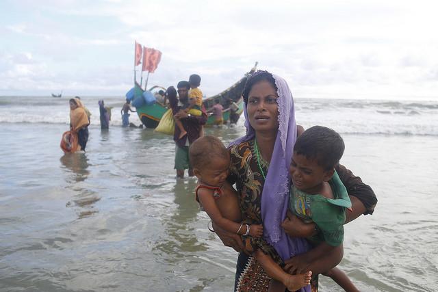 Una madre rohinyá baja de un bote con dos hijos en brazos, a su llegada a Shahparir Dip en Bangladesh, cerca de la frontera con Myanmar (Birmania), durante la huida desesperada de miles de miembros de esa minoría de su país en agosto de 2017, cuando se desató una virtual limpieza étnica en su contra. Crédito: IPS