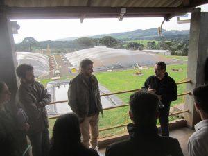 Airton Kunz, jefe de Investigaciones de Embrapa Cerdos y Aves, explica a visitantes el Sistema de Tratamiento de Efluentes de la Porcicultura de la Granja São Roque, parte visible detrás suyo, en Videira, en el sureño estado de Santa Catarina, el mayor productor y exportador de carne de cerdo de Brasil. El biogás, la bioelectricidad y el biometano son subproductos surgidos de la necesidad de dar destino ecológico a los excrementos porcinos. Crédito: Mario Osava/IPS