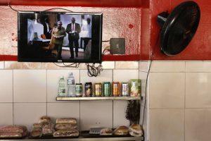 La pantalla de un televisor en una cafetería de La Habana, muestra aRaúl Castro, primer secretario del Partido Comunista de Cuba, y el prsidente Miguel Diaz–Canel, cuando se disponen a votar durante la sesión extraordinaria de La Asamblea Nacional del Poder Popular, el parlamento local. Crédito: Jorge Luis Baños/IPS