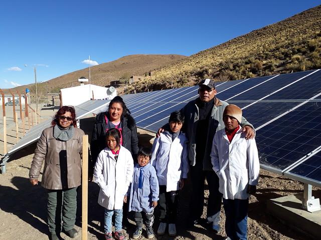Algunos pobladores de San Francisco, una comunidad de apenas 54 habitantes en la Puna argentina, junto a los paneles fotovoltaicos estrenados a principios de octubre, que abastecen toda su electricidad y les permite por primera vez tener alumbrado público. Es el cuarto pueblo completamente solar de la provincia de Jujuy, fronteriza con Bolivia y Chile. Crédito: Daniel Gutman/IPS