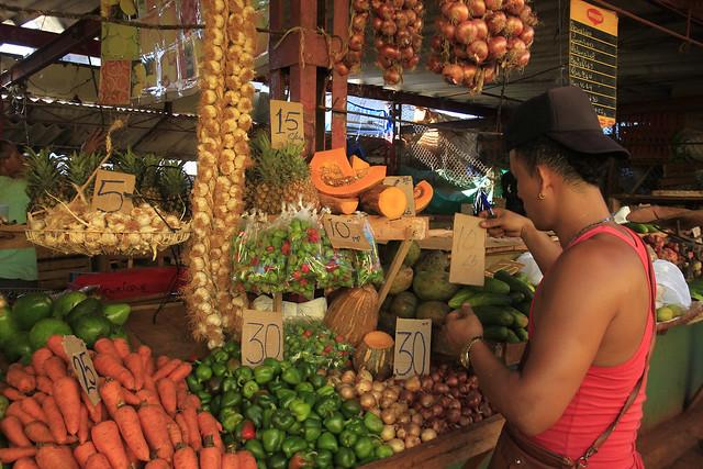 Un empleado coloca cartones con los precios sobre algunas hortalizas en un agromercado de gestión privada en Playa, uno de los 15 municipios que conforman la capital de Cuba. Crédito: Jorge Luis Baños/IPS