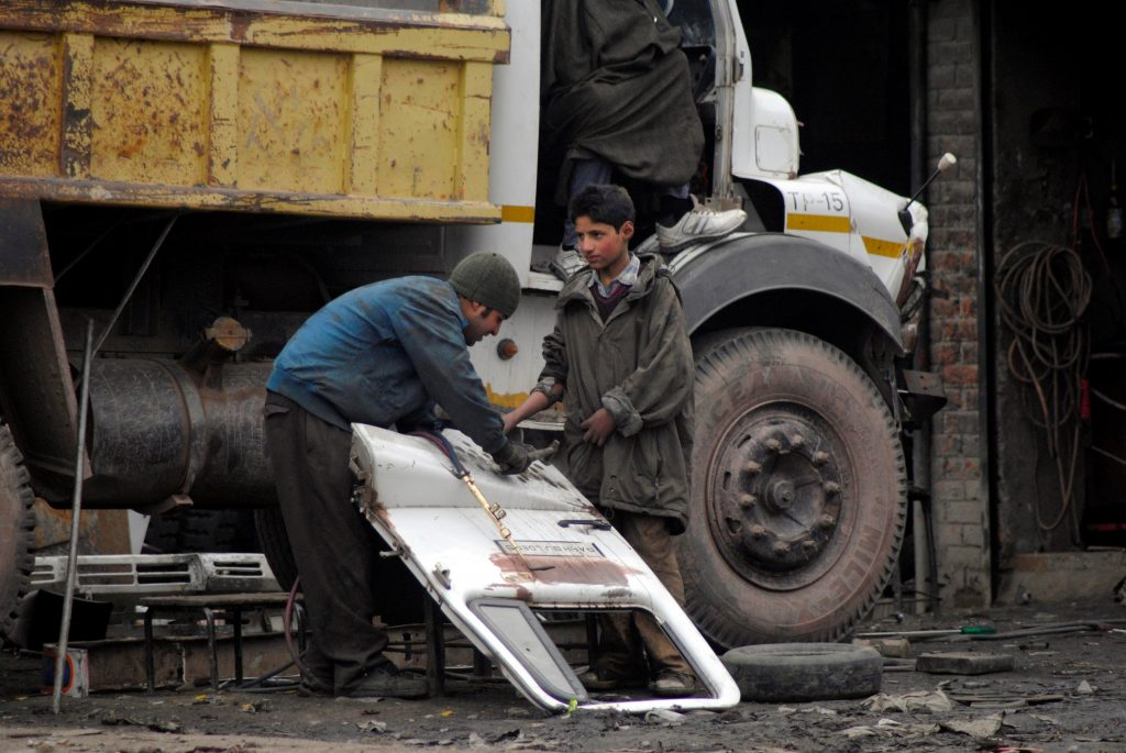 Un niño trabaja en un taller de reparación de vehículos en Cachemira, en India. Un nuevo estudio indica que los centros financieros mundiales, como el neoyorquino Wall Street o la City de Londres, al igual que las grandes instituciones bancarias deberían desempeñar un papel importante en la liberación de los 40,3 millones de personas sometidas a esclavitud moderna. Crédito: Umer Asif / IPS