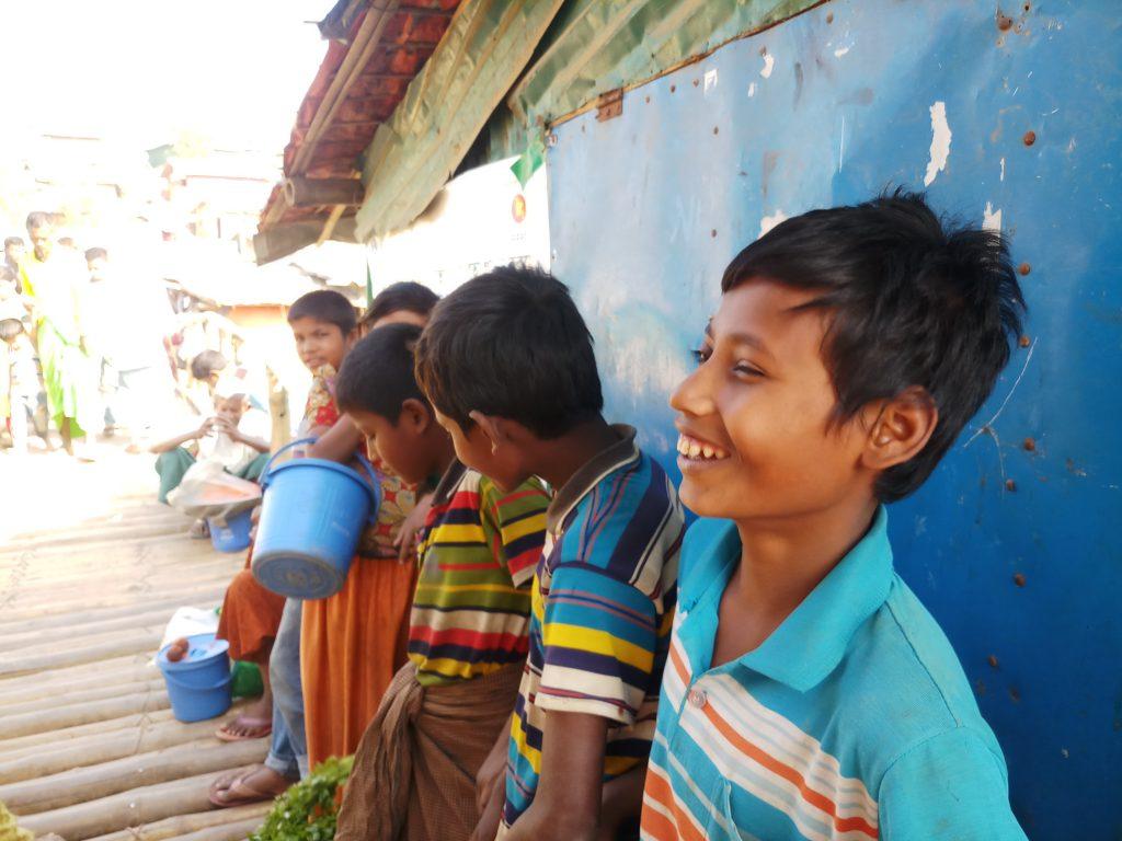 Mohammad Rafique (primero a la derecha) y otros niños en el campo de refugiados rohinyás de Kutupalong, en Cox's Bazar, mientras vendían verduras el 11 de marzo. Ahora la cuarentena nacional en Bangladesh para contener la pandemia de covid-19 ha aislado el campo, del que no se puede salir o entrar y donde el distanciamiento físico es una recomendación impracticable dado su nivel de hacinamiento. Foto: Rafiqul Islam / IPS
