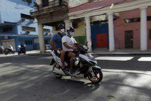 El líder del club cubano de Moto Eléctrica Osdany Fleites Nuñez traslada a su padre a una consulta médica, en el capitalino municipio de Centro Habana, en La Habana. Se calcula que actualmente unas 200 000 motocicletas eléctricas transitan por la capital cubana. Foto: Jorge Luis Baños/IPS