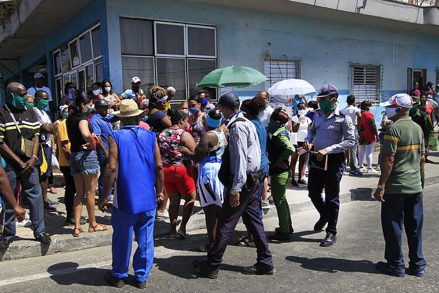 Agentes de la Policía Nacional Revolucionaria de Cuba tratan de organizar en una fila a compradores aglomerados en el exterior de una tienda de alimentos, en el municipio de Marianao, en La Habana, donde la clientela no guarda la distancia interpersonal preceptiva para contener el contagio de la covid-19. Foto: Jorge Luis Baños/IPS