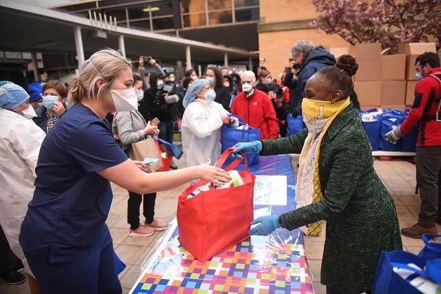 Una mujer afroamericana entrega una bolsa de asistencia a una sanitaria blanca, en uno de los operativos por la pandemia de covid en la ciudad de Nueva York. Foto: Alcaldía de Nueva York