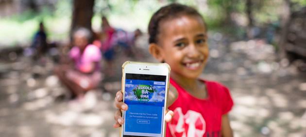 """Una niña de Timor-Leste muestra la plataforma en línea que utilizará para estudiar mientras su escuela está cerrada debido a la pandemia covid-19. La Unesco aboga por incluir a todos los niños, niñas y jóvenes bajo una consigna: """"Todos significa todos"""". Foto: Bernardino Soares/Unicef"""