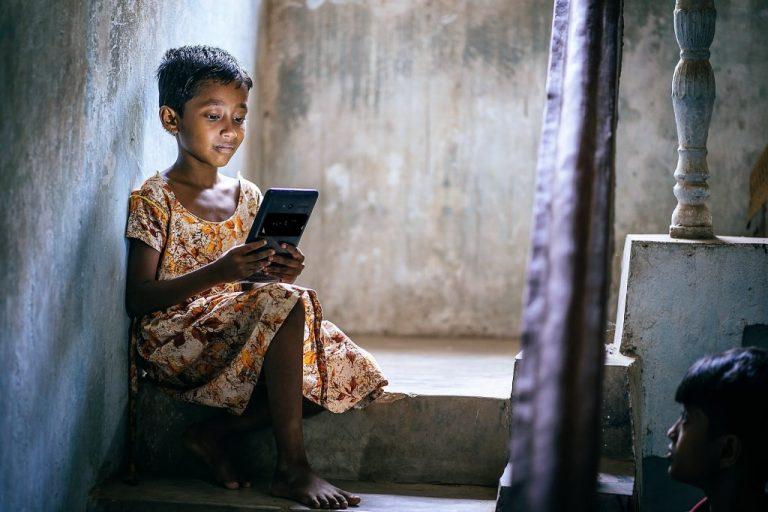 Una niña en un barrio pobre y hacinado de Bhubaneswar, en India, revisa sus tareas de aprendizaje electrónico en una tableta. Foto: Cortesía de John Marshall / Aveti Learning