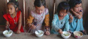 Niñas en Laos comen crema de arroz en un programa sostenido por el Fondo de las Naciones Unidas para la Infancia (Unicef). Mejorar la producción de alimentos y el acceso a dietas saludables es una recomendación de la FAO para frenar el hambre en el mundo. Foto: Jacqueline Labrador/Unicef