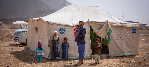 Una familia de yemeníes desplazados por el conflicto en un campamento a las afueras de la ciudad de Marib. La guerra civil, más la crisis económica, eventos climáticos adversos y la pandemia covid-19 amenazan la seguridad alimentaria de millones de habitantes. Foto: Olivia Headon/OIM