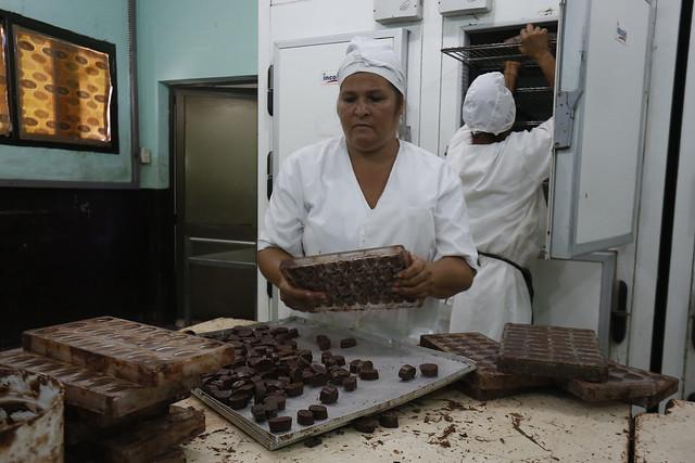 Dos empleadas elaboran bombones artesanales en la fábrica de chocolate Rubén David Suárez Abella, en el municipio de Baracoa, en la oriental provincia Guantánamo. Las minindustrias de los municipios cubanos crean fuentes de empleo para mujeres y jóvenes asociados a labores tradicionales y no tradicionales del sector agropecuario. Foto: Jorge Luis Baños/IPS