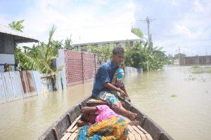 Arif Hossain en su pequeña embarcación transita por una inundada calle del distrito de Lohajang , en el centro de Bangladesh. Este sastre dejó de tener trabajo en su oficio y ahora sobrevive trasportando personas en su bote. Muchos de los bangladeshíes que viven en 33 de los 64 distritos del país han perdido sus viviendas, sus cosechas y su ganado por las inundaciones. Foto: Farid Ahmed / IPS