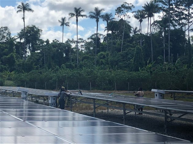 Dos mujeres realizan mantenimiento en la granja de paneles solares de Pokigron, un poblado de agricultores y pescadores surinameses cuya vida ha mejorado sustancialmente desde que acceden a electricidad basada en energía solar. Foto: Luis Pérez/BID