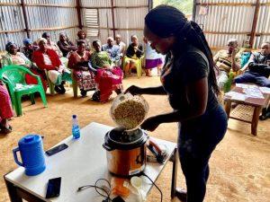Una capacitadora muestra a integrantes de una pequeña comunidad rural de Kenia como se cocina en una olla eléctrica. Foto: Fiona Lambe/SEI