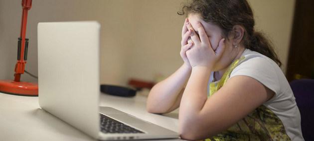 Una adolescente se tapa la cara con las manos ante una computadora portátil, asustada por las noticias que lee sobre la pandemia. Foto: Dusko Miljanic/Unicef