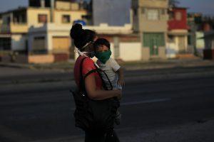 Una mujer con su pequeño hijo en brazos, ambos protegidos con mascarillas, camina por una calle del municipio de Marianao, en La Habana, Cuba. Tener un solo hijo o ninguno es la opción muchas mujeres cubanas. Foto: Jorge Luis Baños/IPS