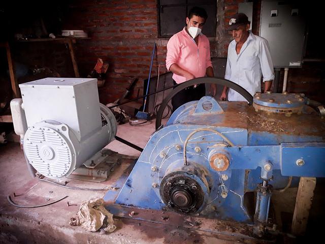 Neftalí Membreño (D), encargado del cuarto de máquinas, revisa el funcionamiento de la turbina y el generador de la minicentral hidroeléctrica del caserío Potrerillos, en el municipio de Carolina, en el departamento de San Miguel, en el este de El Salvador. Esta pequeña comunidad rural, donde viven unas 24 familias, logró en 2006 instalar una pequeña presa para autoabastecerse de electricidad y a bajo costo. Foto: Edgardo Ayala/IPS - Hidroelectricidad comunitaria ilumina caseríos salvadoreños