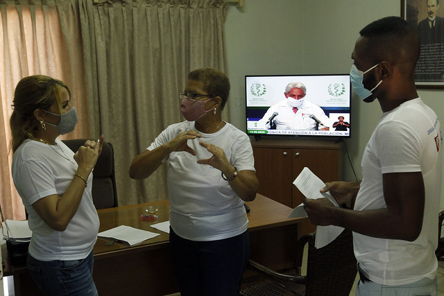 Tres personas usando la Lengua de Señas Cubana en una oficina.