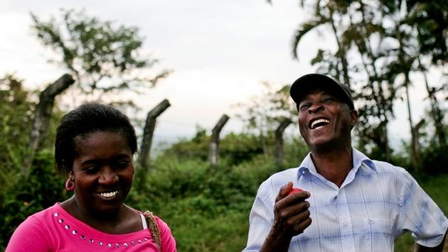 Dos afrodescendientes Latinos riendo en un campo.
