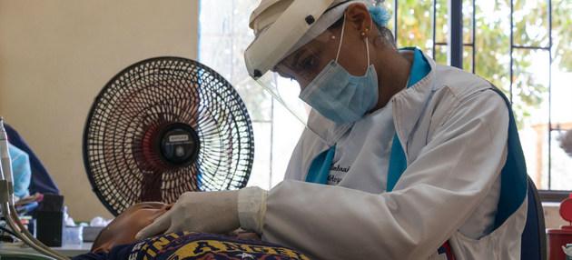 Una trabajadora de la salud examina a un niño colombiano durante la pandemia. Médicos, enfermeros y demás trabajadores de la salud pagan un alto precio en vidas y salud en el combate a la covid-19, que hace estragos en América Latina. Foto: Cruz Roja Colombia.
