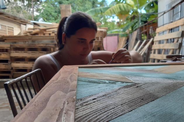 Shallya Sánchez, lideresa y fundadora de EcoDeco Taller da los últimos retoques a un cuadro de madera personalizado con colores específicos para un área de spa y masajes. Sede del emprendimiento en el barrio de Palatino, en el municipio de Cerro, en La Habana. El uso en Cuba de madera reciclada garantiza bajos costes de las materias primas, lo que amplía su accesibilidad. Foto: Cortesía para IPS de EcoDeco Taller