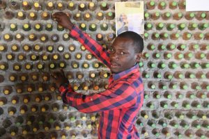 David Mande muestra una pared de una casa construida con ecoladrillos, elaborados con botellas plásticas rescatadas de la basura que se rellenan con tierra húmeda que luego se endurece. Cada botella se cierra herméticamente para que terminen transformándose en paredes firmes y convertirse así en solución sostenible y barata al déficit de vivienda en Uganda. Foto: Wambi Michael / IPS