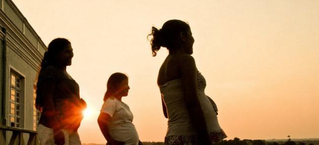 Tres mujeres afectadas por covid en embarazadas viendo al horizonte durante el atardecer.
