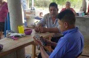 Hombre emplea dispositivos digitales en su microempresa en Honduras como parte de la digitalización Inclusiva.