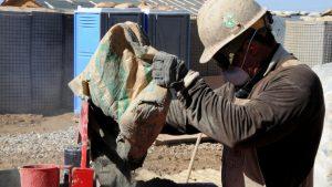 Obrero con cubrebocas vertiendo bolsa de cemento en máquina, muestra de uno de los millones de trabajos perdidos.