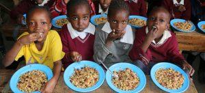 """Niños en Kenia disfrutan un almuerzo con vegetales desestimados para la exportación por no tener la forma """"estéticamente correcta"""". No desperdiciar alimentos y mejorar las dietas puede contribuir con el clima, según el Pnuma. Foto: Martin Karimi/PMA"""