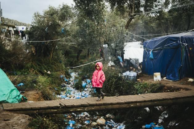 Una niña solicitante de asilo de Afganistán camina sobre un puente precario dentro de lo que se conoce como El Olivar, un campamento improvisado adyacente al centro de recepción e identificación de Moria en la isla griega de Lesbos. Foto: Achilleas Zavallis/Acnur