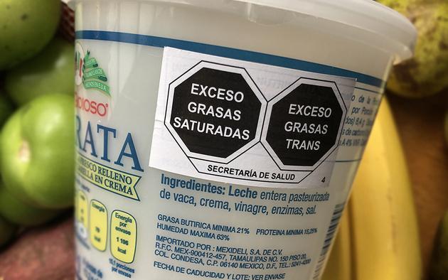 Envase mostrando las etiquetas negras en forma de octágono que pretenden combatir la obesidad en México.