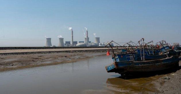 Chimeneas humeantes de una central eléctrica junto al río Hai en su desembocadura en el mar de Bohai, en China. Foto: Shutterstock / YPPicturesPro