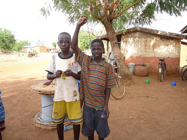 Dos hermanos adolescentes en una zona rural de Ghana con las ondas que han elaborado para espantar los pájaros del arrozal familiar. Los sueños de educación para la población infantil y adolescente se dificultan para los países del Sur en desarrollo de bajos ingresos, en especial en zonas rurales. Foto: Albert Oppong-Ansah/IPS