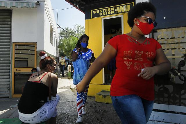 Transeúntes pasan por delante de una de las sucursales en La Habana de la compañía estadounidense Western Union, que gestiona el envío de remesas en Cuba desde la nación norteamericana. La empresa es una de las pocas que mantiene el servicio de transferencias a la isla, luego que el Departamento del Tesoro estadounidense prohibió hacerlo a los bancos. Foto: Jorge Luis Baños/IPS