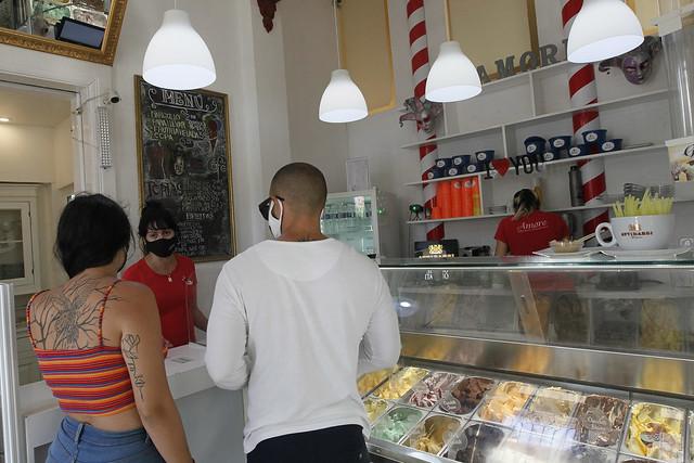 Una dependienta atiende en La Habana a dos clientes en una heladería de gestión privada, durante la tercera fase de la respuesta de Cuba a la covid-19. Alrededor de 40 por ciento de los más de 600 000 trabajadores autónomos en la isla suspendieron temporalmente sus negocios por el cierre de actividades económicas para contener la pandemia. Foto: Jorge Luis Baños /IPS