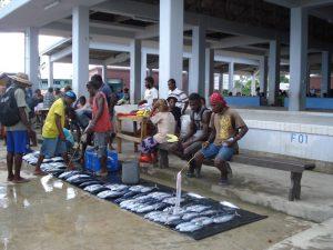 Hombres mostrando pescado en el piso como parte de la pesca de subsistencia.