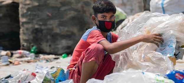Un niño de 12 años clasifica desechos plásticos peligrosos sin ninguna protección, en Daca, la capital de Bangladesh, en una ocupación con la que busca apoyar a su familia, donde los adultos se quedaron sin trabajo tras el cierre de las actividades para controlar la expansión de la covid. Foto: Parvez Ahmad/Unicef