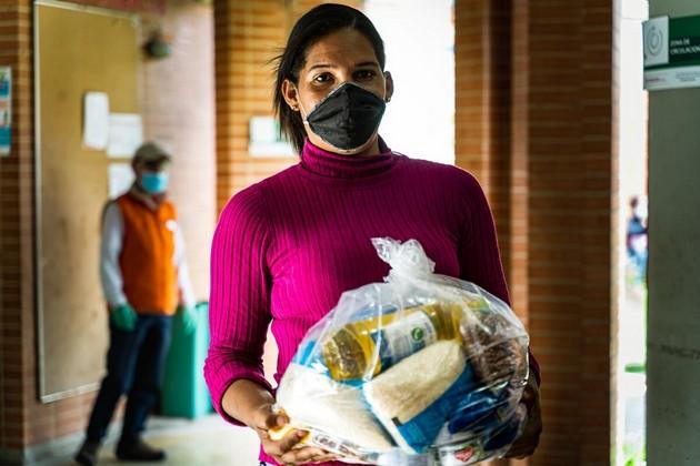 Dayana, una migrante de Venezuela, recibe ayuda con comestibles del Programa Mundial de Alimentos en Bogotá. Asistir a migrantes y desplazados en los países de acogida es un requisito para combatir el hambre en tiempos de pandemia. Foto: PMA